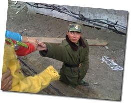 Chinese soldier shaking hands with children at Nathu La